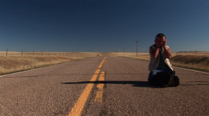 Gordon Hempton recording light wind in the prairie as it sweeps across an unused highway (Photo: Martin DiCicco)